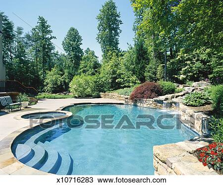 Swimming pool, hot tub and waterfall in back yard Stock Image