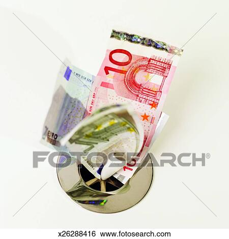 Close Up Of Euro Bank Notes Going Down The Drain Stock Photograph