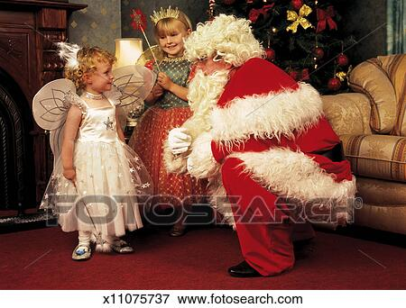 Man dressed as Santa talking to two little girls in fairy outfits - Picture Of Man Dressed As Santa Talking To Two Little Girls In Fairy