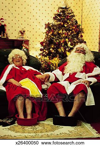 Portrait Of Mr And Mrs Claus Sitting On Couch With