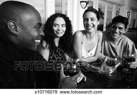 Black And White Portrait Of Two Young Couples Drinking Wine Talking