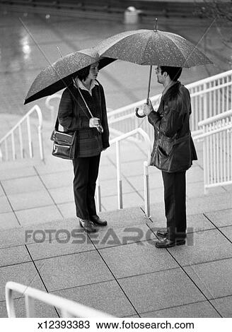 People With Umbrellas Talking On Stairs