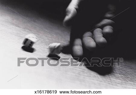 Close-Up of a Hand Rolling Dice Stock Photo