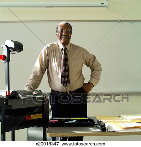 Picture Of Teacher Standing At Desk With Over Head Projector