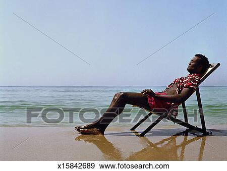 52c89b4b4b Man sitting in deck chair on beach, eyes closed, side view Stock Photo