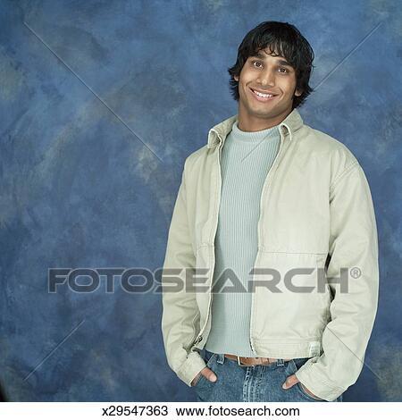 Uno, ritratto, di, uno, etnico, uomo, in, uno, luce, colorato, giacca, e, uno, blu, maglione, con, suo, mani, in, suo, tasche, sorrisi, a, il,