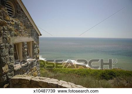 stock photograph of side profile of a stone cottage on a waterfront rh fotosearch com