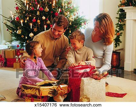 family in a living room and children opening christmas presents