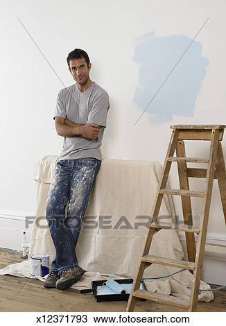 Homme Pencher A Mur Blanc Dans Salle Préparé Pour Décoration Côté A Escabeau Et Peindre Cylindre Banque D Image