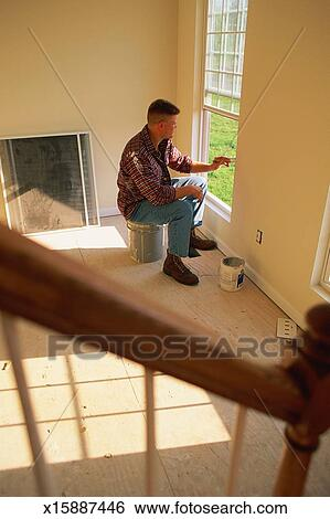 Man painting window frame inside house Stock Photograph