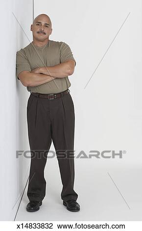 Stock Photo of Portrait of a mature man leaning against a wall ...