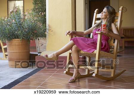 Miraculous Young Woman Sitting In A Rocking Chair With A Drink Stock Pdpeps Interior Chair Design Pdpepsorg