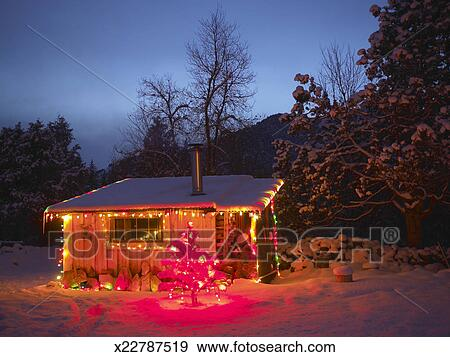 Log Cabin Christmas.Log Cabin Decorated With Christmas Lights In Snow At Night Stock Photo