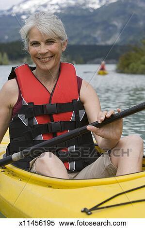 stock image of portrait of mature woman in kayak wearing life jacket
