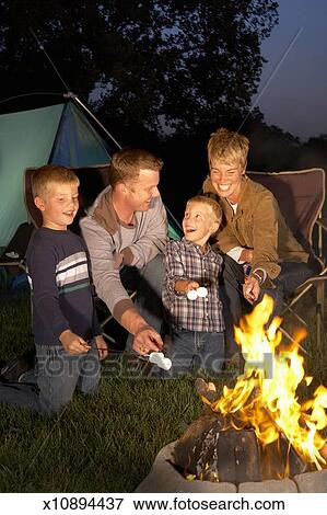 Family With Two Sons 4 6 Years Roasting Marshmallows Around Campfire
