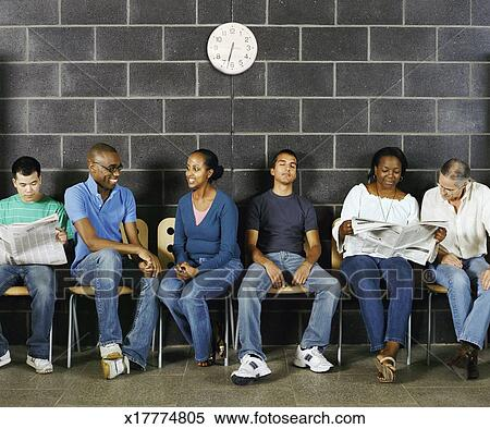 stock image of group of students sitting reading newspapers talking