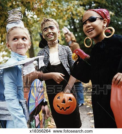 boy and two girls in halloween costumes do trick or treat