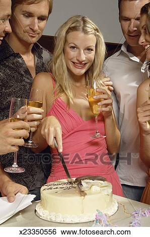 Young Woman Cutting Birthday Cake Friends Holding Champagne