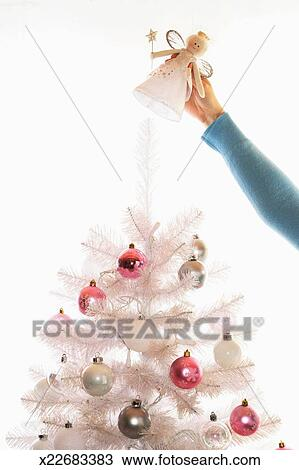 Stock Photo Of Woman Placing Angel On Top Of Fake White Christmas