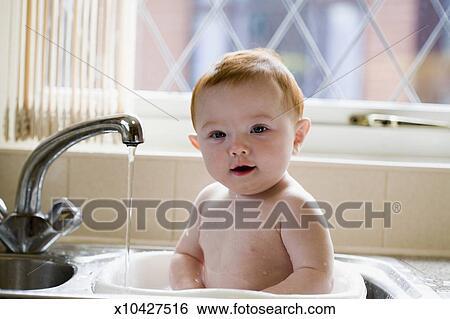 Baby Girl 6 9 Months Taking A Bath In Kitchen Sink Portrait Stock Photograph