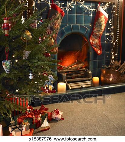 Christmas Presents Under Tree.Christmas Presents Under Tree In Front Of Decorated Fire Place Stock Photograph