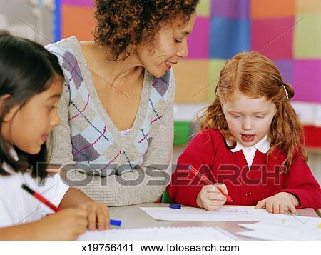 Teacher Sitting At Table Watching Schoolgirl 5 7 Writing