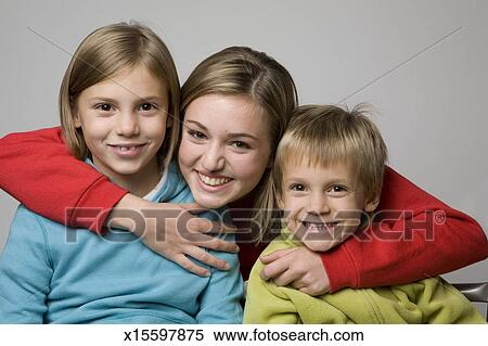 stock image of portrait of teenage girl 14 15 hugging two younger