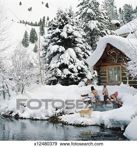 Group of Friends in Hot Tub Outside Snowy Winter Lodge Stock Photo