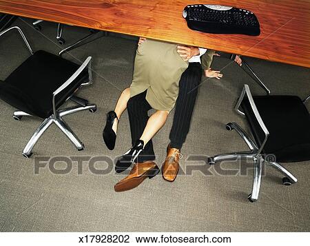 Banque de photo couples affaires embrasser sous bureau vue