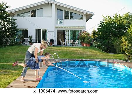 Mother helping daughter (5-7) clean swimming pool by house, side ...