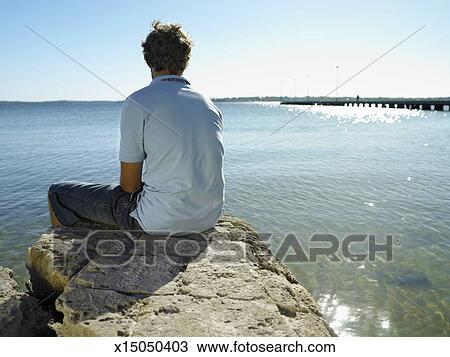 stock photo of man sitting on rock facing sea rear view x15050403