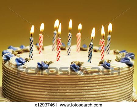 Nine Lit Candles And Blue Decorative Flowers On Birthday Cake