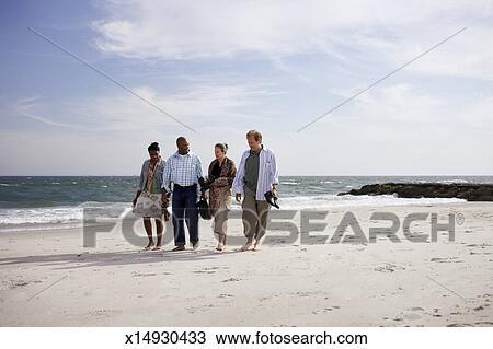 Two Couples Walking Along Beach Talking Stock Image X14930433
