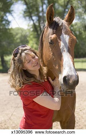 Stock Images of Woman patting American Quarter horse, outdoors x13095396 - Search ...