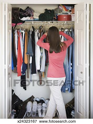 Teenage Girl (15 17) Looking At Clothing In Bedroom Closet, Rear View