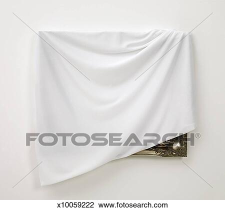 Stock Photo of White cloth draped over picture frame, revealing ...