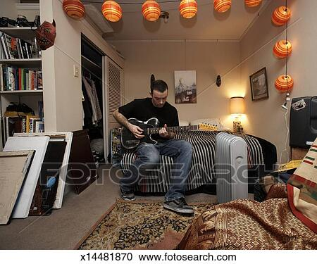 Stock Photography Of Man Playing Electric Guitar On Bed In Art