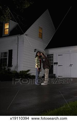 Boy (12-13) kissing girl (12-13), girl turning head, in driveway in front  of house, side view, night Picture