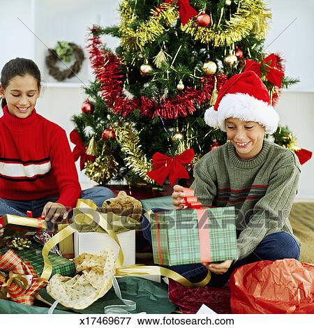 picture sister and her brother sitting in front of a christmas tree opening their presents