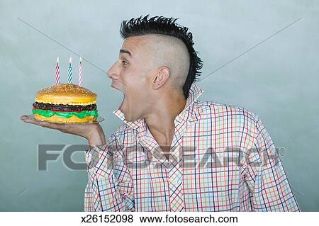 Awesome Man With Mohawk Holding Hamburger Birthday Cake Stock Photo Funny Birthday Cards Online Inifodamsfinfo