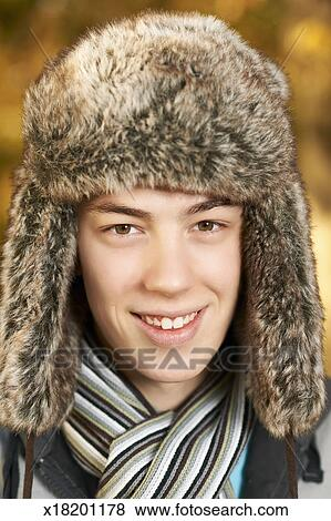 Picture - Teenager male wearing fake fur hat. Fotosearch - Search Stock  Photos 1ca7c1ce0df