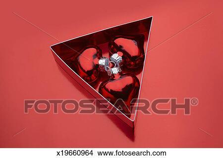 stock photo of three heart shaped ornaments in a triangular box