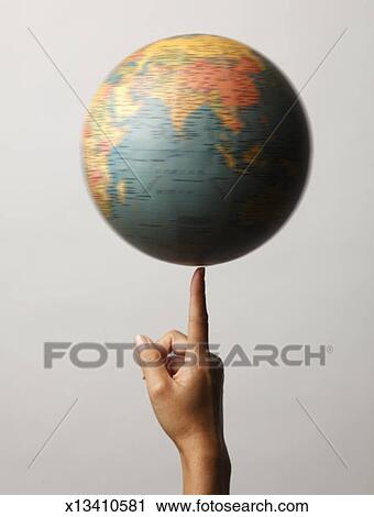 stock photography of globe spinning slowly on finger x13410581