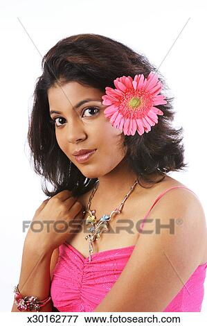 Portrait Of A Young Woman With A Flower Behind Her Ear Stock Photo