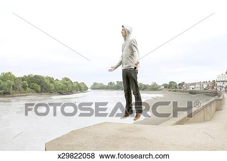 A Man Floating In Mid Air Next To River