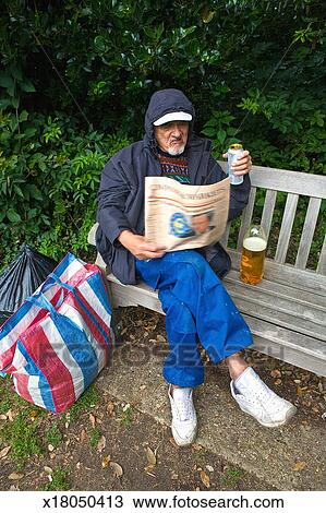 Stock Photo Of A Drunk Man On A Park Bench Reading A Newspaper