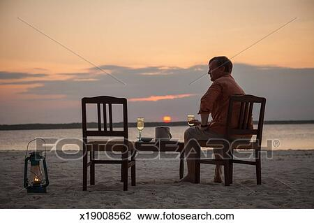 stock photo of man sitting alone at table for two on beach x19008562