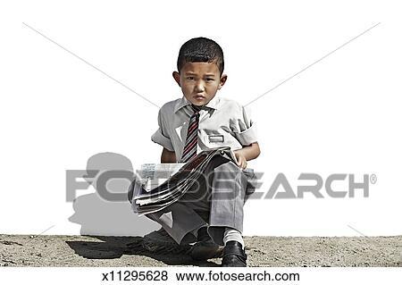 Portrait of Nepali school boy holding a newspaper Stock Photo