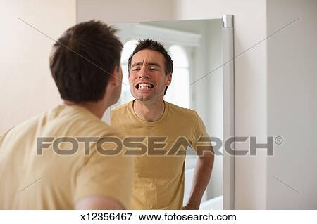 picture of man looking at teeth in mirror x12356467 search stock