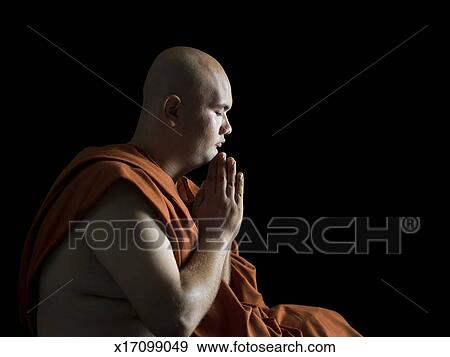 Buddhist Monk Meditating In Dark